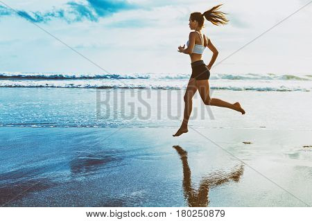 Active sporty woman run along ocean surf by water pool. Sunset sand beach background with blue sky and sun. Woman fitness jogging workout and sport activity on summer holiday.