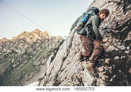 Climber Man climbing rocky mountains with backpack Travel Lifestyle concept adventure summer vacations outdoor mountaineering sport risk and endurance