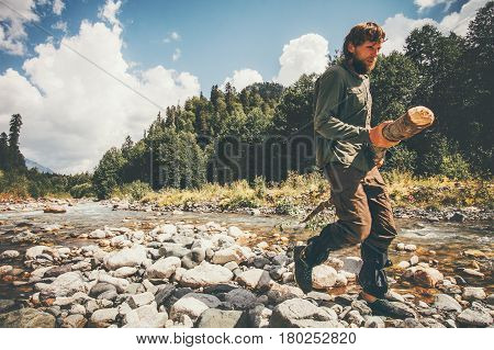 Man traveler lumberman holding wood Travel survival Lifestyle concept adventure summer vacations outdoor wild forest and river on background
