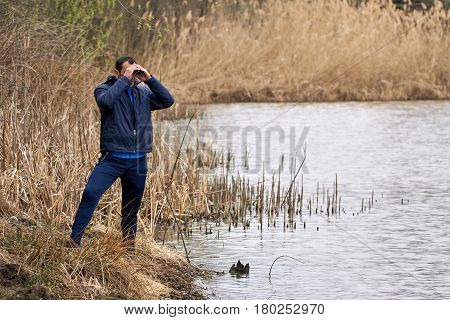 Man Watching Birds By The Lake