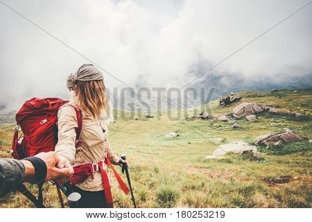 Couple travelers Man and Woman holding hands follow at foggy mountains landscape on background Love and Travel happy emotions Lifestyle concept. Young family traveling adventure vacations