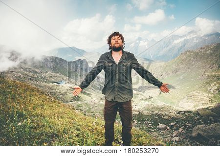 Happy Man hiking meditating in mountains Travel Lifestyle concept adventure summer vacations outdoor hiking mountaineering bearded wayfarer