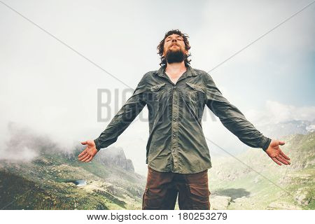 Man meditating in mountains getting energy hand raised Travel Lifestyle concept adventure summer vacations outdoor hiking mountaineering bearded wayfarer