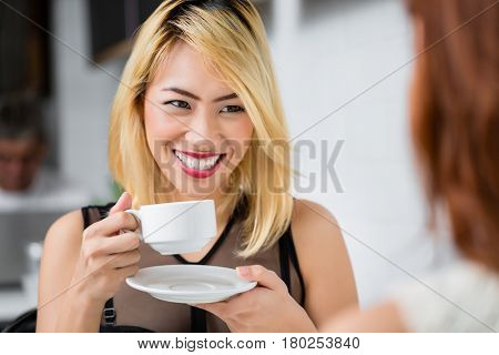 Beautiful blond Asian woman drinking coffee and smiling at her friend as they enjoy refreshments in a cafeteria, close up over the shoulder view of her face