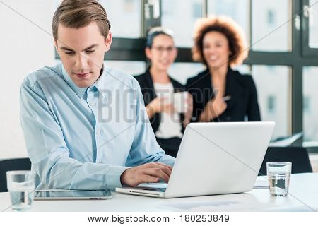 Young dedicated man working on laptop while reading information from a PC tablet in the office