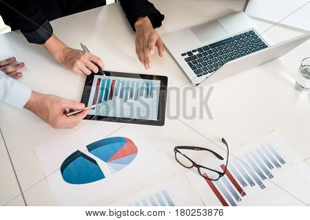 Three members of a professional team analyzing ascendant bar chart displayed on tablet PC