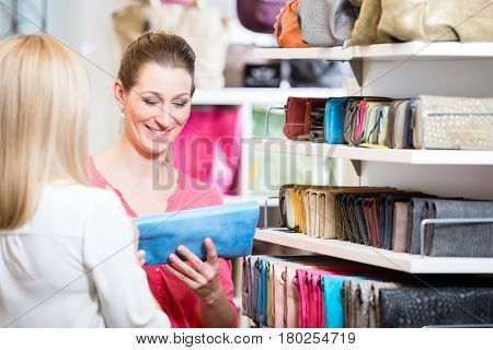 Female customers in store shopping looking for wallets and purses