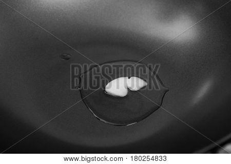 Coconut oil melting in wok, closeup