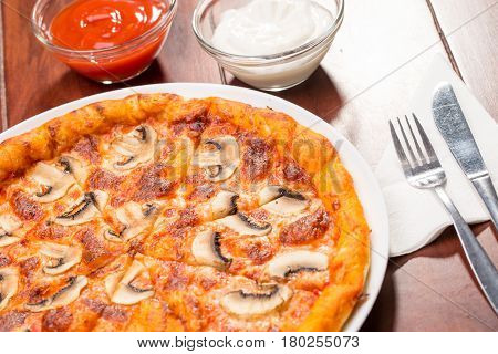 Pizza mushrooms on a wooden table with ketchup and sauce