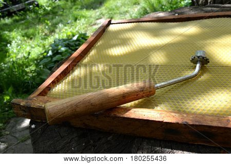 Wax spur lying on the beehive frame with wax foundation