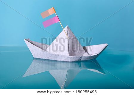 Paper boat made from notebook paper. Origami paper ship sailing on blue water surface.