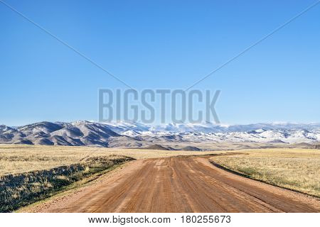 Dirt ranch road at foothills in northern Colorado with distant Rocky Mountains covered by snow