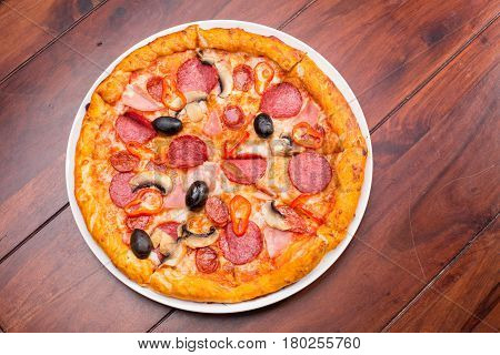 Italian Pizza With Salami, Cheese, Mushrooms And Olives On A Wooden Table