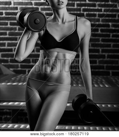 Do you lift Vertical cropped monochrome shot of a sporty young woman working on her biceps lifting weights showing off her stunning body