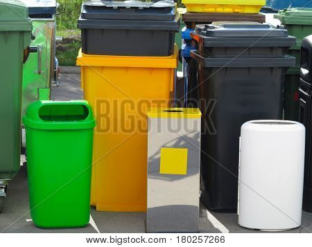 A lot of different colorful garbage bin containers.