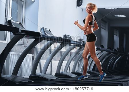 Horizontal full length shot of a happy young fitness woman smiling to the camera while working out at the gym running on a treadmill copyspace lifestyle healthcare body abs muscles strength energetic.