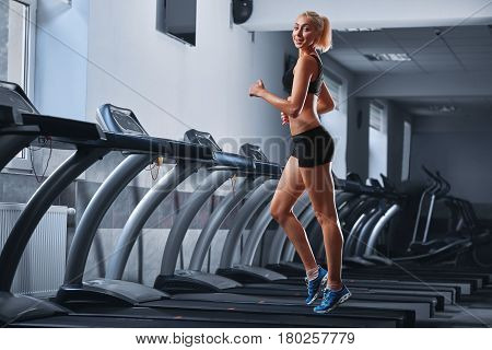 Gorgeous sporty girl smiling to the camera while training at the gym jogging on a treadmill copyspace confidence beauty positivity lifestyle runner running run endurance activity athletics concept.
