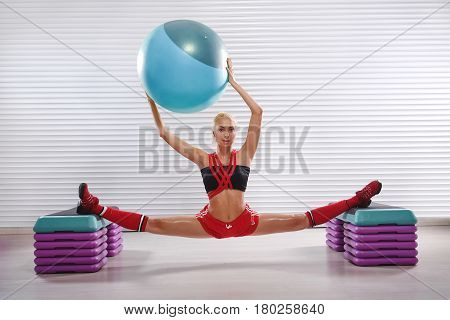 Full length shot of a beautiful young woman practicing gymnastics doing slits holding a fit ball working out at the health club strength power muscles agility energy athlete activity lifestyle.