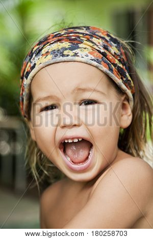 Portrait of a crying baby with a kerchief on her head asian-mestizo close-up
