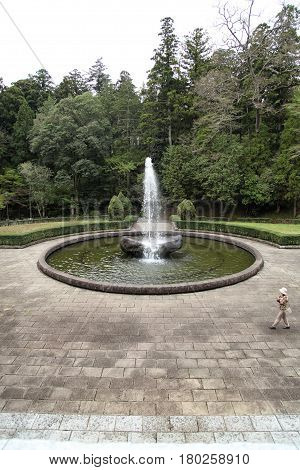 Female tourist walking around a fountain in Naritasan Temple Narita Japan 16. april 2012
