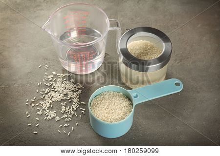 Kitchen ware with rice and water on table