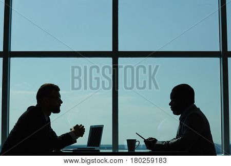 Profile view of two confident business partners conducting negotiations while sitting in modern dim boardroom against panoramic window