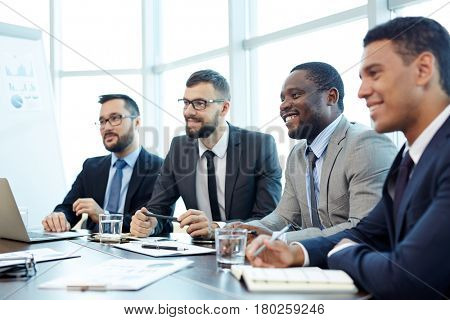 Multiethnic group of employees listening to presentation of their team leader while sitting at meeting table and taking notes, waist-up portrait