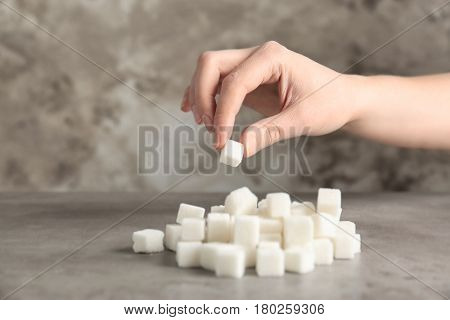 Female hand taking sugar cube from table