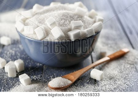 White sand and lump sugar in bowl on wooden background