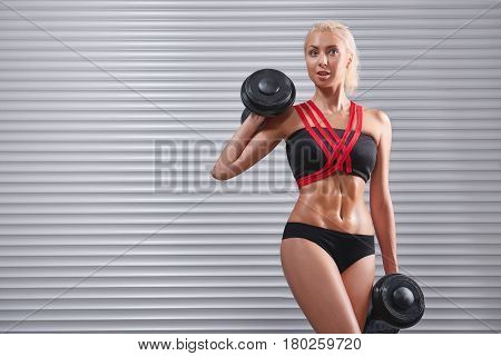 Beautiful cheerful young fitness woman in workout clothing top and shorts smiling to the camera working out with dumbbells showing off her hot sexy perfect muscular body strength power bodybuilding.