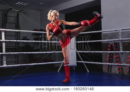 Full length shot of a female fighter wearing boxing gloves practicing her high kick on a boxing ring training working out exercising preparing fight victory confidence determination endurance energy.