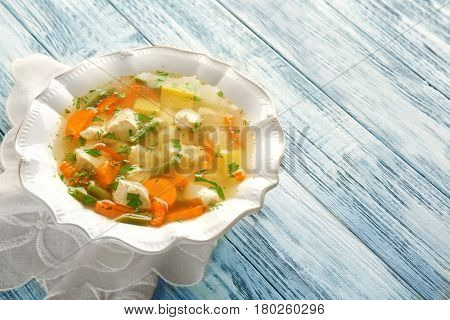 Plate with chicken soup on wooden table