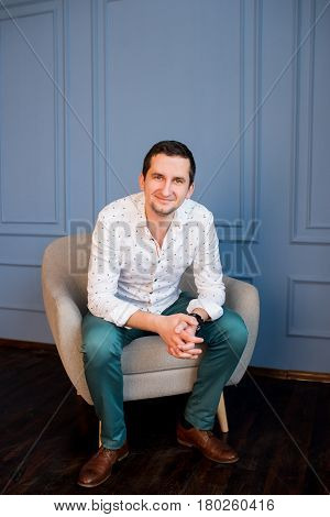Happy handsome young businessman in white shirt and green trousers sitting in armchair and looking at camera