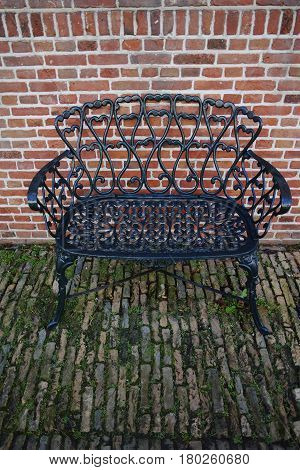 Decorative wrought iron bench in the garden near old brick wall