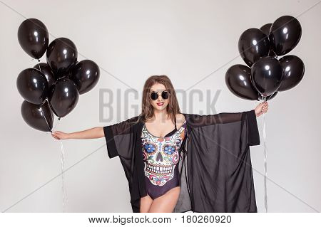 Beautiful woman in combination holding bundles of baloons on a white background.