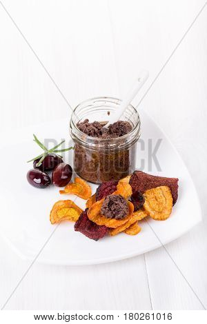 Tapenade - olive paste made from kalamata olives and vegetable chips. Copy space.
