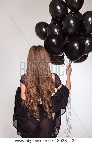 Girl with long hair standing with her back to the camera and holding a bundle of baloons.