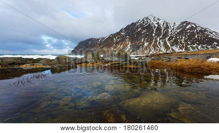 Landscape of Lofoten islands with reflection in a water on the foreground in winter