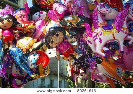 Street vending Colorful cartoon foil balloons depicting cartoon characters. Public holiday near Perpignan Tourist Office .Perpignan France 14.07.2014.