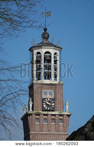 Old church tower with bells clock and weather vane