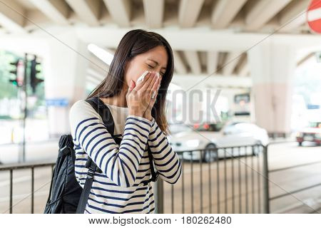 Woman sneezing in Hong Kong city