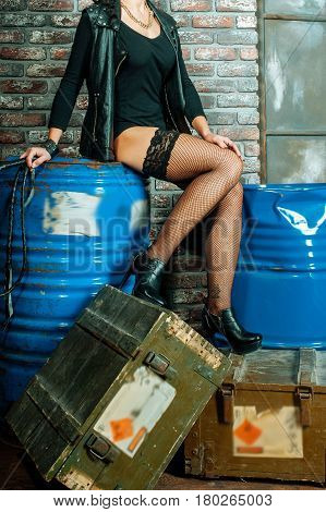 feminine crossed legs in fishnet black stockings. Wamp girl in garage sittinh on old wood boxes and blue metal tanks.