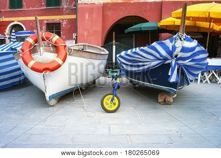 Two old fishing boats, exposed in the main square of the village of Vernazza (Liguria, Northern Italy), part of the Cinque Terre UNESCO Site.