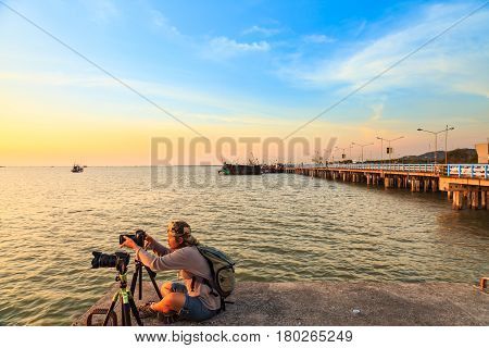Tourist woman takes the pictures of sunset at coastal bridge in Chonburi named Chonlamarkwithi 84th anniversary Thailand