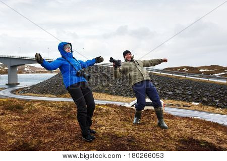 Two photographers bended under a strong gust of wind in Lofoten winter time