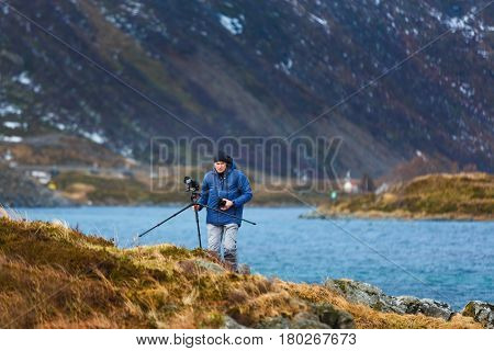 The photographer with tripod is walking on the hill of Lofoten islands winter time