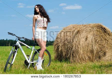 brunette girl on bicycle in the field