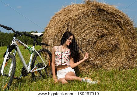 attractive young  woman sitting on haystack outdoors