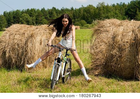 emotional brunette cycling on the field outdoors