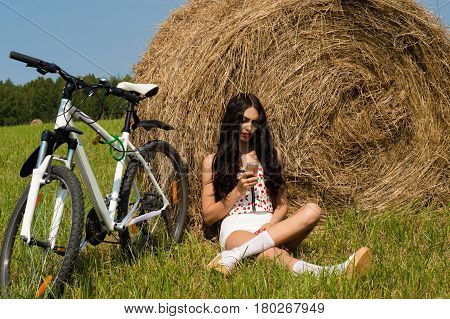 fashionable woman sitting on haystack with iphone